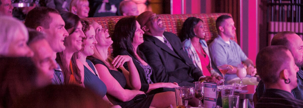 guest laughing during a punchliner comedy club show on a carnival cruise ship