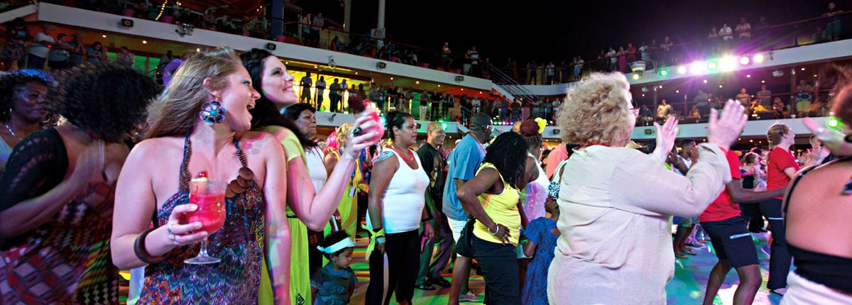 Carnival cruise vacationers dancing on the Lido deck at the Mega Deck Party