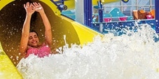 a woman splashing at teh end of the twister waterslide